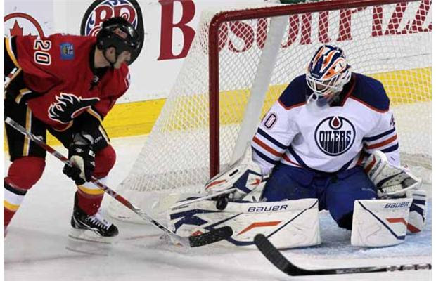 Calgary Flames Curtis Glencross tries to score past the Edmonton Oilers goalie Devan Dubnyk at the Saddledome in Calgary on Sept. 25, 2011.