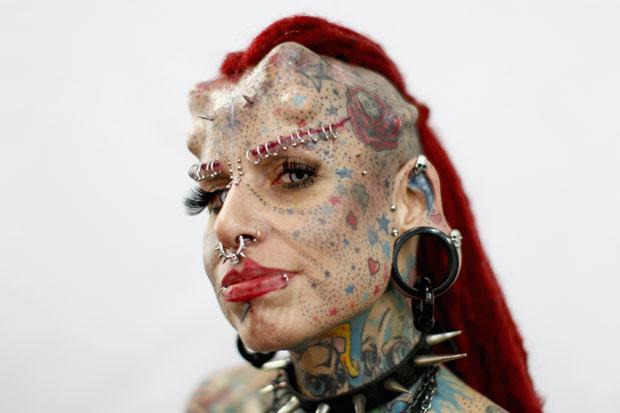 Um festival de tatuagem realizado em Caracas, na Venezuela, contou com a participação de alguns fãs 'extremos' de tattoos e de modificações corporais nesta sexta-feira (27). Uma das participantes que mais chamou a atenção foi Mary Jose Cristerna, mais conhecida como 'Mulher Vampira', que além do rosto tatuado possui piercings, alargadores nas orelhas e implantes que modificam a aparência de sua cabeça. (Foto: Jorge Silva/Reuters)