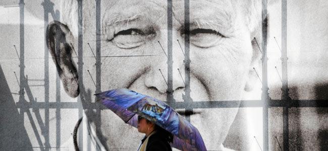 Una mujer pasa frente a un cartel con la fotografía de Juan Pablo II en Cracovia