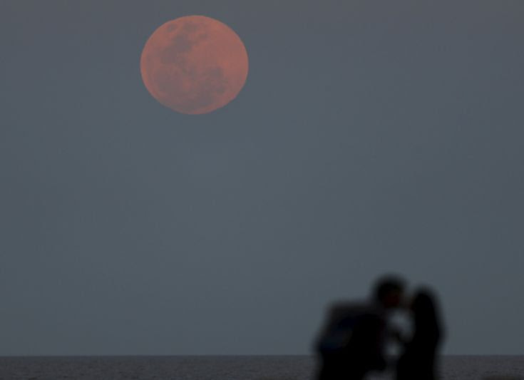 A couple kisses as a supermoon rises in the sky over the Rio de La Plata in Buenos Aires