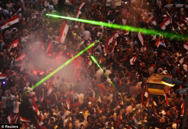 Laser lights are flashed as protestors gather in Tahrir Square to celebrate the removal of President Morsi this evening