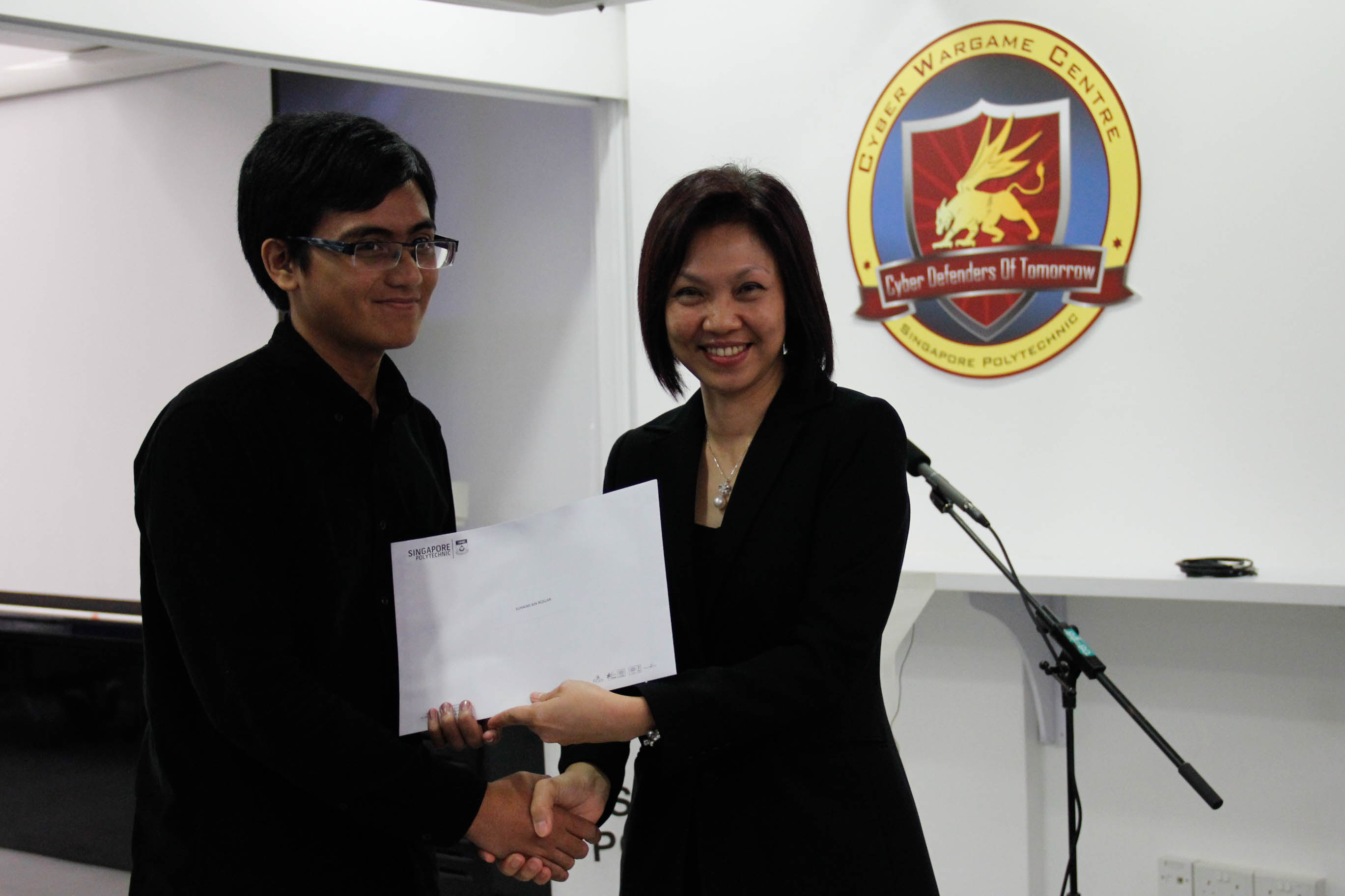 DMIT Director Ms Georgina Phua presenting Certificate of Participation in DISM CTF S1 to year 2 student Suhaimi