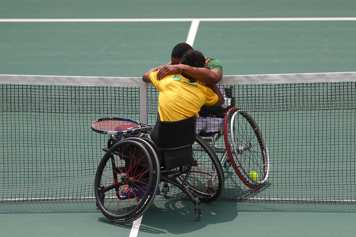 Lucas Sithole of South Africa and Ymanitu Silva of Brazil hug after competing in wheelchair tennis.