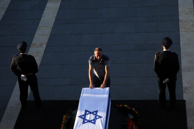 "An Israeli man pays his respects at the coffin of former Israeli president Shimon Peres at the plaza outside the Knesset, Israel""s Parliament, on September 29, 2016 in Jerusalem."