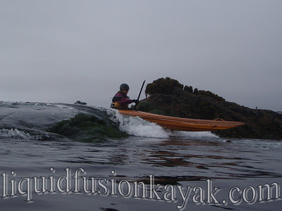 Cate takes the strip built sea kayak in the rocks.