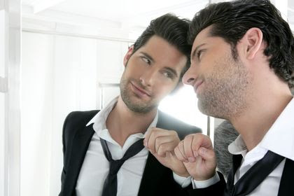 A man enjoying his reflection in the mirror.