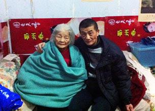 图片:鲍俊生出狱后,在家中与母亲合照。(家人提供)