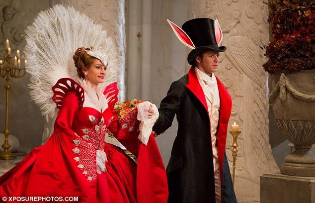 Atraente: Roberts é escoltado pelo belo príncipe que usa uma roupa combinando vermelho e preto para o baile à fantasia