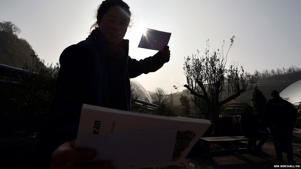 A woman watches the eclipse of the sun through pinhole camera  at the Eden Project