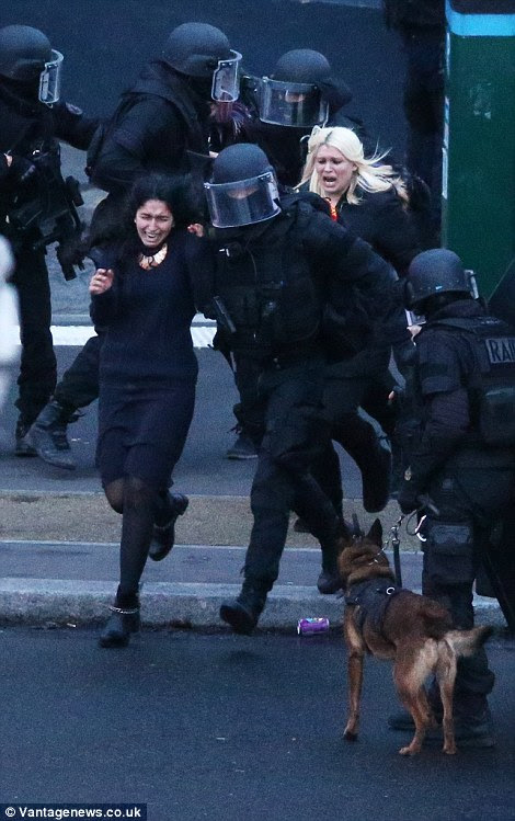 A woman runs from the building in tears