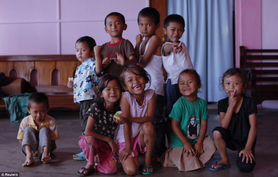 Todos os sorrisos: Engi, cinco, é o mais novo dos filhos de Ziona. Ela é cercada por outros jovens membros da família na aldeia