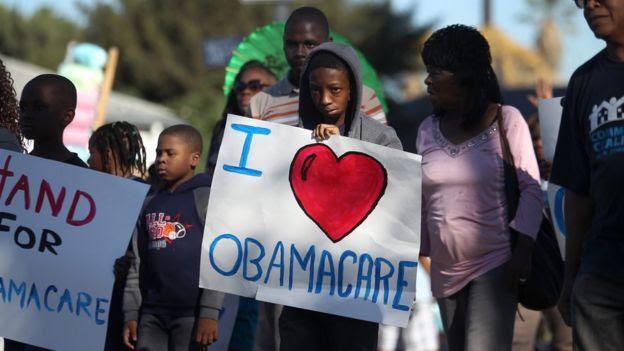 Niño con cartel a favor del Obamacare