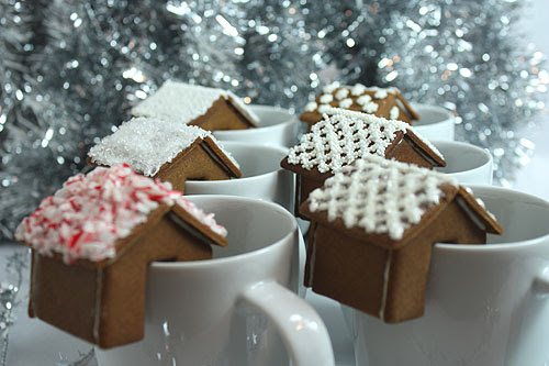 gingerbread house that sits on the edge of a mug