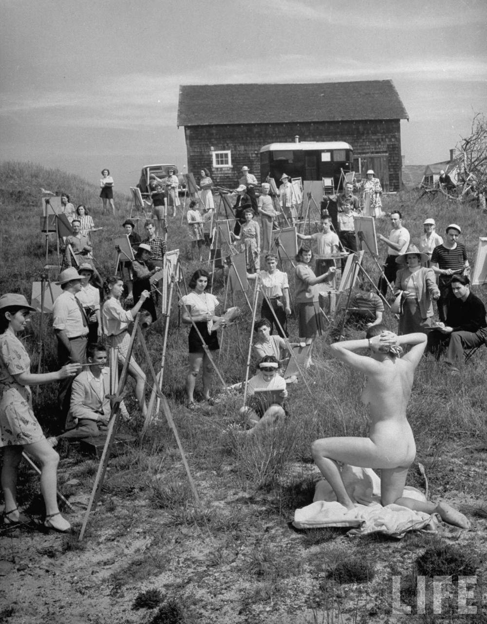 Andreas Feininger: Nude model posing for a large group of art students of the Farnsworth Art School working at easels outdoors on a gentle hillside. Cape Cod, MA, US. July 1946