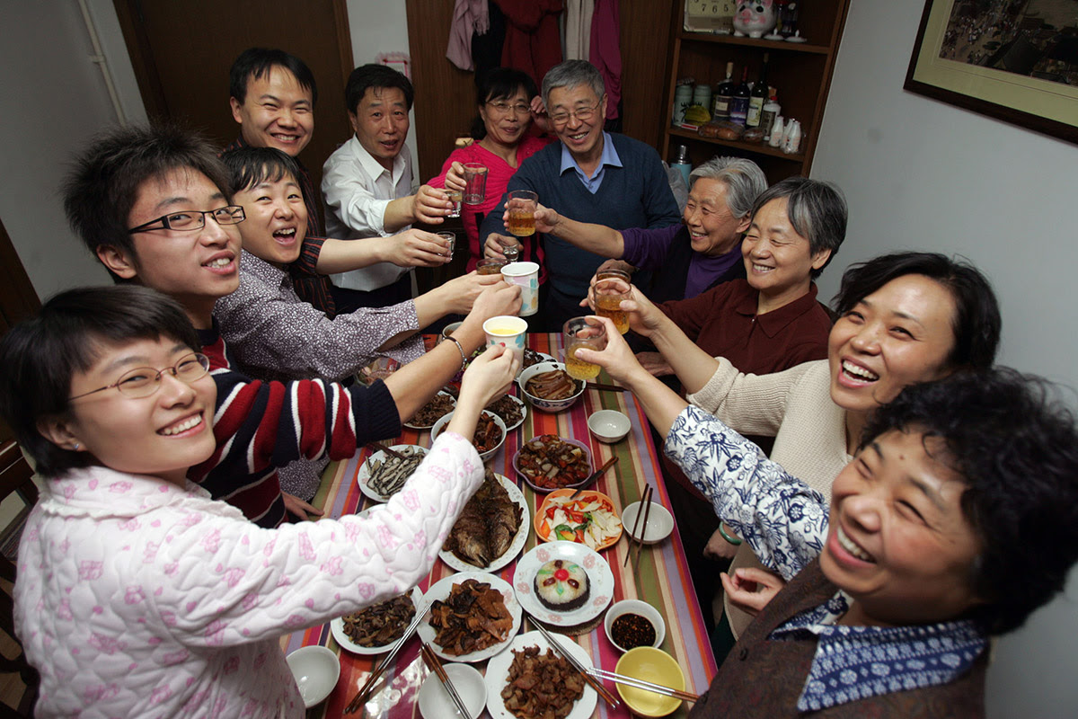 Members of a family toast during New Year's Eve dinner at a home in Beijing. The most important custom is a Reunion Dinner on New Year's Eve. Chinese families will get together for a huge meal, always centred around a fish dish