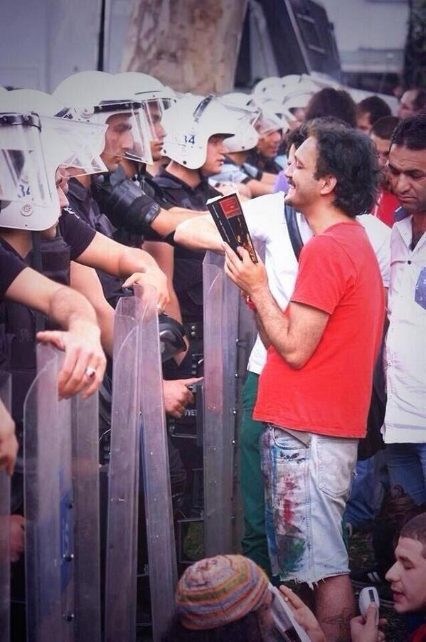 During Thursday's protests, a young man reads from a book to the police.