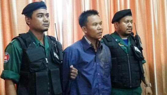 Police stand next to Oeut Ang earlier this month at the Phnom Penh Municipal Police headquarters after he was arrested for the murder of political analyst Kem Ley. Photo supplied