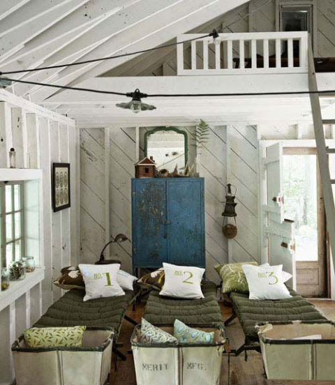 A row of antique wood cots and vintage hampers fill this kids' cabin with plenty of opportunities and room to host sleepovers for friends. Canvas number-print pillows were handmade.
