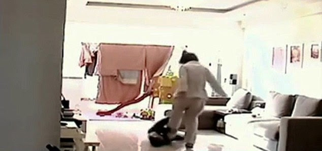 Attack: In a sickening abuse of power, Heng, wearing a cream trouser suit, towers over the boy kicking him while he uses his legs to try and fight her off.