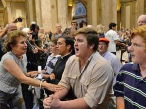 """Una mujer pretende hacer callar a los que intentaban apagar con sus rezos la celebración del 75 aniversario de la """"Noche de los Cristales Rotos""""."""