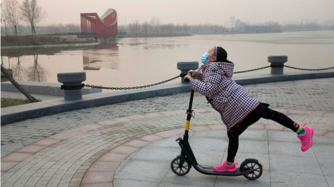 A child on a scooter enjoys the outdoors during a day of relatively lighter pollution during the first-ever red alert