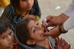 A Pakistani health worker administers the polio vaccine…