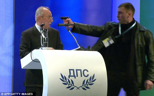 Bulgarian politician Ahmed Dogan looks at the gunman as he holds a gun at his head and misfires