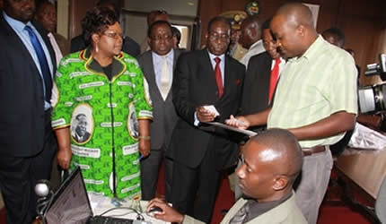 President Mugabe, Vice President Mujuru, national chairman Cde Simon Khaya Moyo and political commissar Cde Webster Shamu check on the new electronic party membership card from officials at the Zanu-PF headquarters in Harare on March 13, 2013. by Pan-African News Wire File Photos
