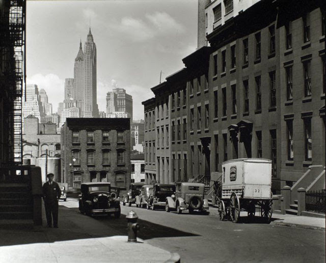 Willow and Poplar Street. Laundry wagon, cars, along sloping street lined with rowhouses, skyline of Manhattan visible above buildings at end of the street.