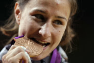 Bronze medalist Marti Malloy of the United States bites the medal during the medal ceremony after the women's 57-kg judo competition at the 2012 Summer Olympics, Monday, July 30, 2012, in London. (AP Photo/Paul Sancya)