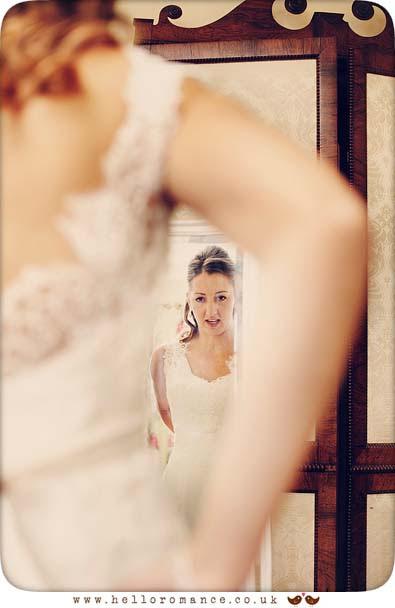 Bride reflected in mirror getting into dress - Hadleigh Wedding Photography Suffolk- Hello Romance