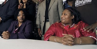 Scott, right, and her sister Gladys Scott wait for a news conference to commence in Jackson, Miss., following their release from prison.  by Pan-African News Wire File Photos