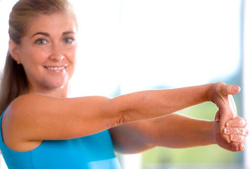 Woman demonstrating elbow stretch exercise.