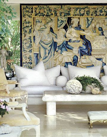Michael Taylor's signature mix of giant white sofa, cannonball pillows, French fauteuils, rustic table.