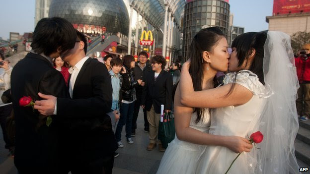 In a picture taken on 8 March, 2011 gay couples kiss during their ceremonial 'wedding' as they try to raise awareness of the issue of homosexual marriage, in Wuhan, in central China's Hubei province