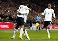 England's Andros Townsend (L) celebrates with Danny Welbeck (2nd L) during their World Cup qualifying match against Montenegro in north London on October 11, 2013