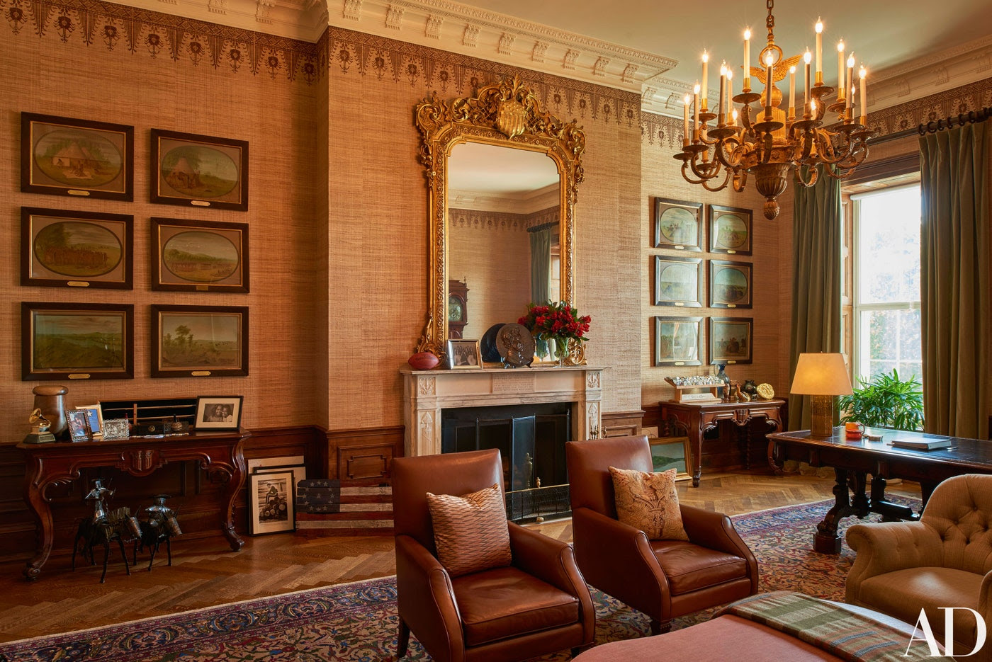 The Treaty Room—filled with memorabilia including one of the President's two Grammy Awards, family photos, and a personalized football—is where Mr. Obama often retreats late at night. He uses the room's namesake table (far right), which has been in the White House since 1869, as a desk. George Catlin scenes of Native American life hang on walls covered in custom-stenciled Larsen abaca. Eighteen-fifties overmantel mirror; 1930s Hereke carpet.