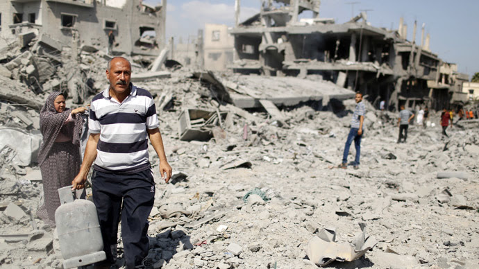 A Palestinian man carries a gas canister that he salvaged from his destroyed house in Beit Hanoun town, which witnesses said was heavily hit by Israeli shelling and air strikes during the Israeli offensive, in the northern Gaza Strip (Reuters)