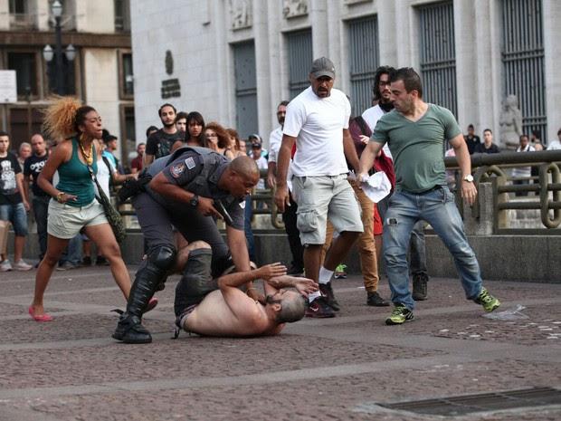 Policial aponta arma para pessoa após apartar briga no Viaduto do Chá (Foto: Marcelo Brandt/G1)