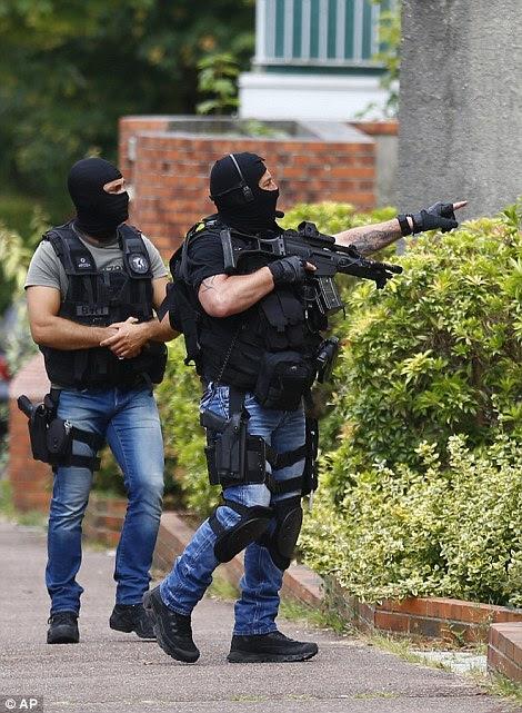 autoridades francesas dizem ter detido um terceiro homem em conexão com o ataque.  Policiais armados são retratados fazendo uma parada em uma casa em Saint-Etienne-du-Rouvray