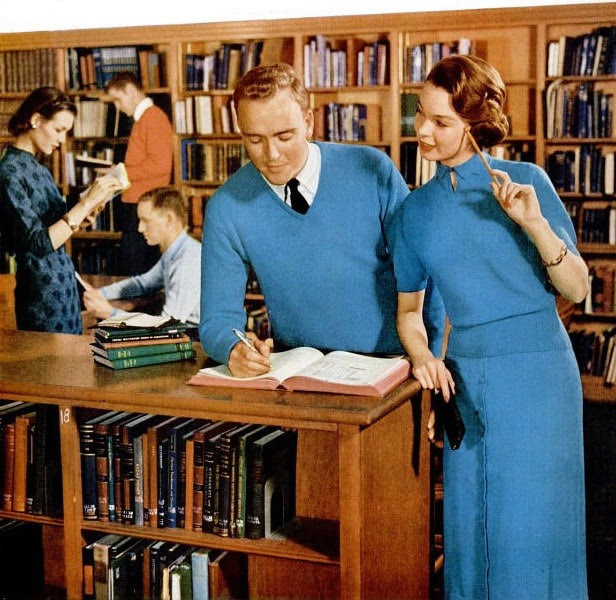 Reading and writing in the library wearing smart knit styles from Kharafleece Sweaters, 1956. That wonderful top-to-toe look. Heavenly sweaters and skirtsin Jantzen-exclusiveKharafleece: purest virginworsted wool, nylon andmiracle vicara… cashmere soft…washable… practicallywrinkleproof.