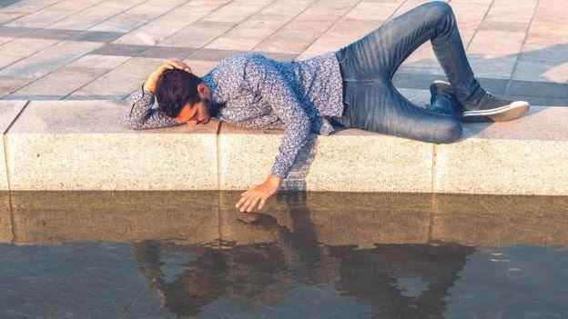 Hombre mirando su reflexión en el agua