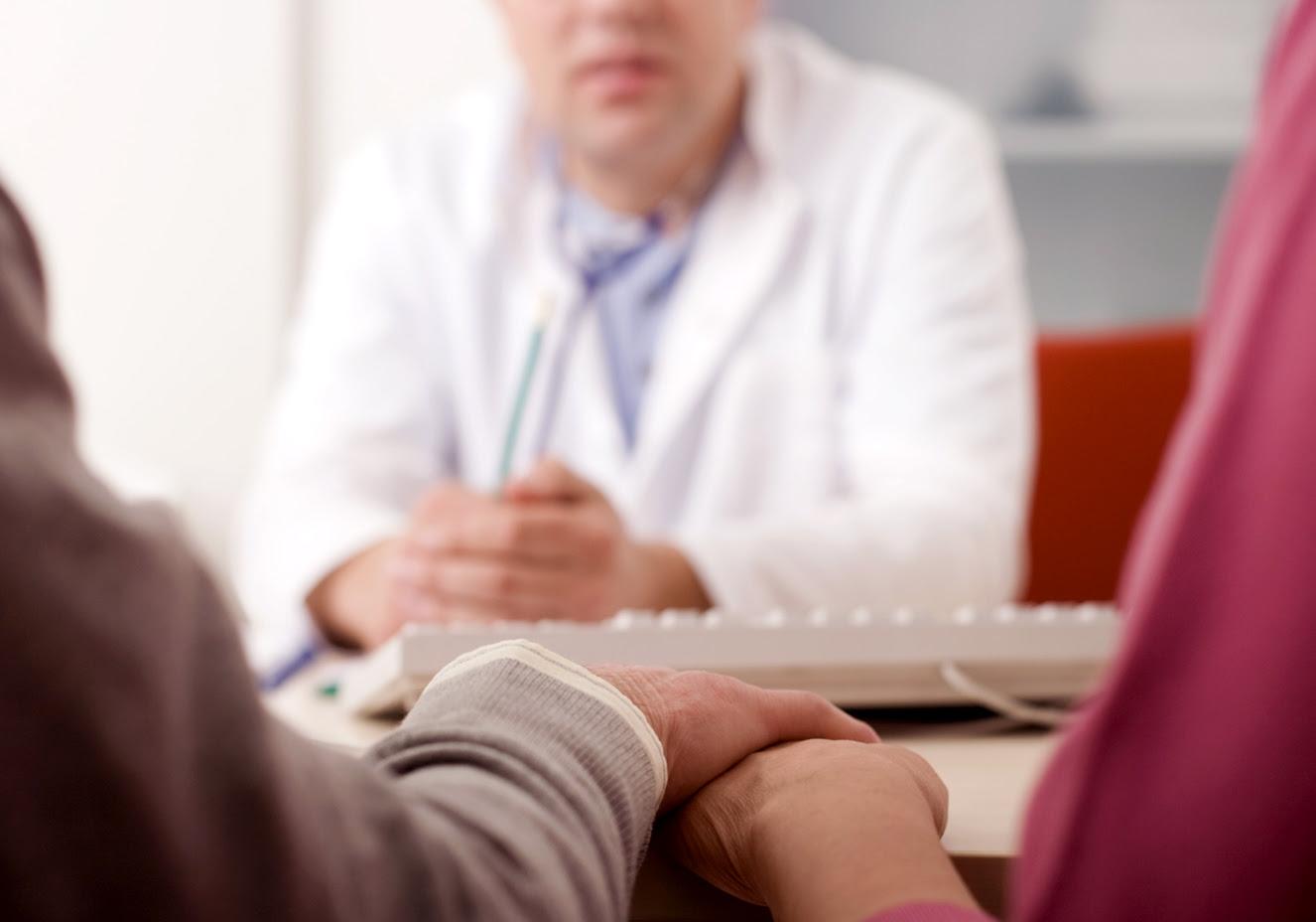 FOTO: Casal de mãos dadas, sentados em frente a um médico