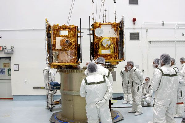 Technicians inspect the GRAIL spacecraft after they are attached to their adapter ring at the Astrotech Space Operations facility in Florida, on August 10, 2011.