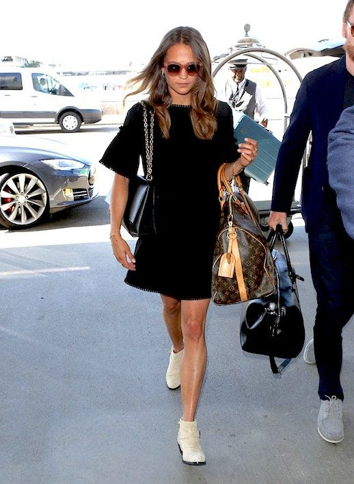 Le Fashion Blog Alicia Vikander Airport Style Black Mini Dress White Ankle Boots Luxury Tote Bag Via Vogue