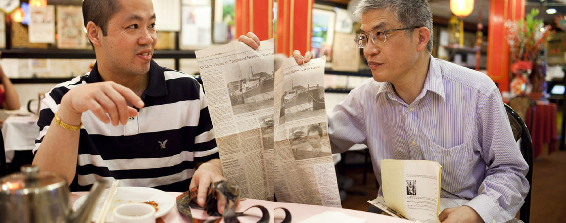 Shengqiao Chen, left, met Zehao Zhou while in prison waiting for asylum. Zhou was his translator. Here, Zhou shares memorabilia with Chen — twenty years after the Golden Venture arrived in the U.S.