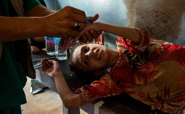 A medic injects an IV into the hand of an Iraqi girl who fled the fighting in the Old City of Mosul as she lies in a clinic in the city's western...