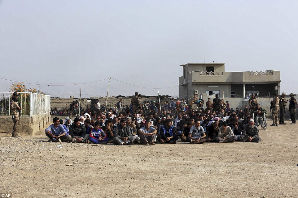 Iraq's elite counterterrorism forces gather villagers for preliminary investigation before taking them to displaced people camps in the village of Tob Zawa, about 9 kilometers (5.6 miles) from Mosul, Iraq