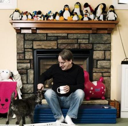 Linus Torvalds sitting bellow penguin collection