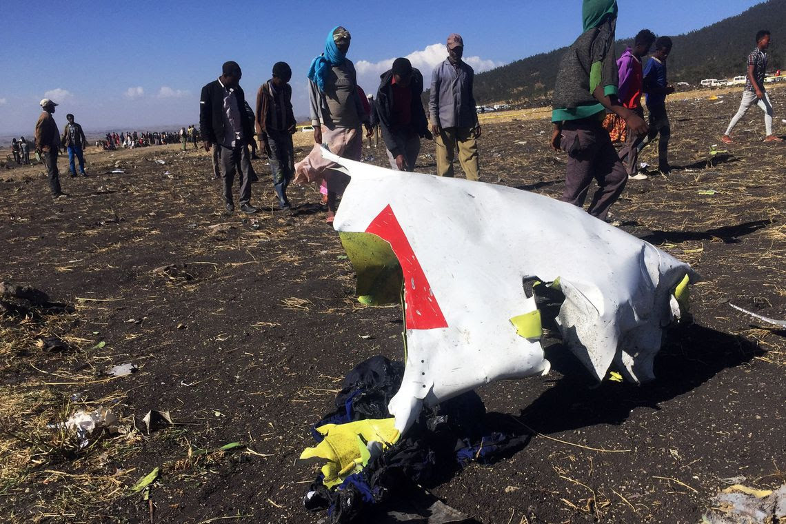 People walk past a part of the wreckage at the scene of the Ethiopian Airlines Flight ET 302 plane crash, near the town of Bishoftu, southeast of Addis Ababa, Ethiopia March 10, 2019. REUTERS/Tiksa Negeri
